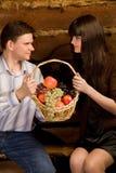 Man en vrouw met mand fruit op bank Stock Foto's
