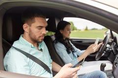 Man en vrouw met smartphones die in auto drijven Royalty-vrije Stock Fotografie