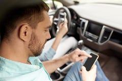 Man en vrouw met smartphones die in auto drijven Stock Foto's