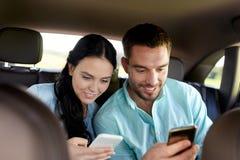 Man en vrouw met smartphones die in auto drijven Royalty-vrije Stock Afbeeldingen