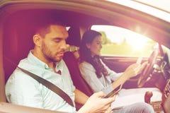 Man en vrouw met smartphones die in auto drijven Stock Afbeeldingen