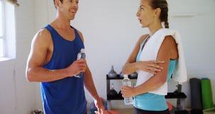 Man en vrouw met waterflessen die aan elkaar spreken 4k stock footage