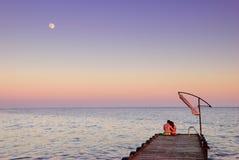 Man en vrouw op een pijler in het maanlicht Stock Afbeeldingen