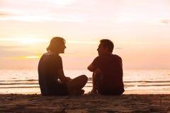 Man en vrouw op het strand bij zonsondergang Stock Foto's