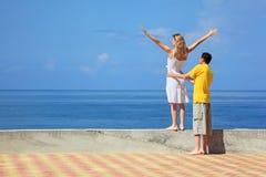 Man en vrouw op kade, vrouw opgeheven handen omhoog Stock Fotografie