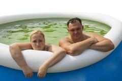 Man en vrouw in opblaasbare pool Stock Foto
