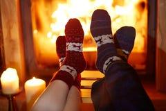 Man en vrouw in warme sokken dichtbij open haard stock foto