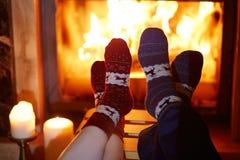 Man en vrouw in warme sokken dichtbij open haard stock fotografie