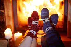 Man en vrouw in warme sokken dichtbij open haard royalty-vrije stock afbeelding