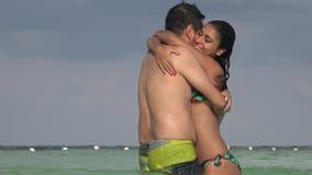 Man en vrouw in zwempakken die pret op vakantie hebben bij oceaan stock video