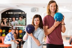 Man en Vrouwen de Ballen van het Holdingskegelen in Club Royalty-vrije Stock Fotografie