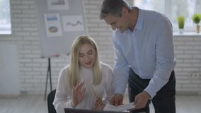 Man en vrouwen de medewerkers werken met laptop die delend bedrijfsideeën in modern bureau spreken Het meisje zit bij bureau stock footage