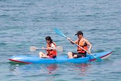 Man en vrouwen die onderaan een overzees kayaking Stock Foto
