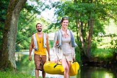 Man en vrouwen dragende kano aan bosrivier Stock Foto's
