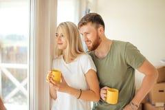 Man en vrouwen het drinken thee dichtbij venster Gekochte nieuw huis of flat stock foto