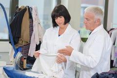 Man en vrouwen het inspecteren kledingstuk stock foto