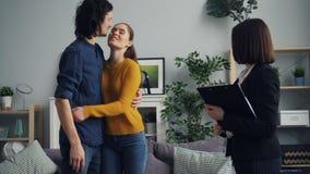 Man en vrouwen het kopen huis die zeer belangrijke het schudden handen met makelaar in onroerend goed nemen die dan kussen stock video