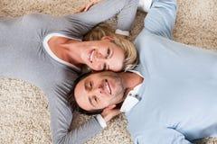 Man en vrouwen het liggen hoofd - - hoofd op het tapijt Royalty-vrije Stock Foto's