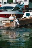 Man en vrouwen het ontspannen op een ligplaats in jachtclub Stock Foto's