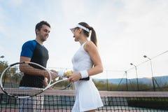 Man en vrouwen het schudden handen na gelijke van tennis royalty-vrije stock foto