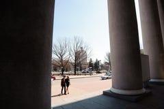 Man en vrouwen het stellen op de straat dichtbij de kolommen van het theater stock foto's