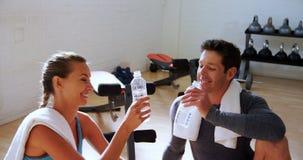 Man en vrouwen roosterende waterflessen bij de gymnastiek 4k stock videobeelden