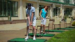 Man en vrouwen speelgolf dichtbij een clubhuis stock video