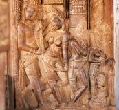 Man en vrouwen in traditionele vorm van Indische die kunst, op de hulp van de steenmuur van de 7de eeuw Hindoese tempel wordt gem Royalty-vrije Stock Afbeeldingen