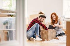 Man en vrouwen uitpakkend materiaal na verhuizing aan nieuw huis royalty-vrije stock afbeelding