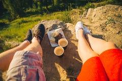 Man en vrouwenbenen op de bovenkant van de heuvel met twee koppen en chocolade Stock Fotografie