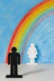 Man en vrouwenpictogrammen met een regenboog en een blauwe hemel Royalty-vrije Stock Afbeelding
