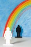 Man en vrouwenpictogrammen met een regenboog en een blauwe hemel Stock Foto's