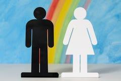 Man en vrouwenpictogrammen met een regenboog en een blauwe hemel Royalty-vrije Stock Fotografie