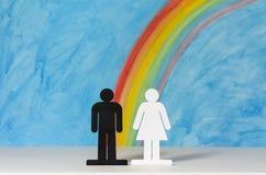 Man en vrouwenpictogrammen met een regenboog en een blauwe hemel Stock Foto