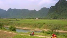 Man en vrouwenritautoped op smalle grondweg langs rivier stock footage