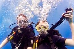 Man en vrouwenscuba-duikers die in tropische overzees omhoog duiken Royalty-vrije Stock Foto
