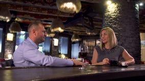 Man en vrouwenteller van de zittings de dichtbijgelegen bar en het drinken wijn en koffie stock videobeelden