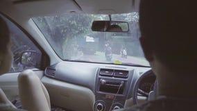 Man en vrouwenzitting in auto, die ergens op landelijk oostelijk tropisch gebied berijden stock video