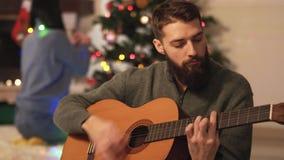 Man en vrouwenzitting dichtbij Kerstmisboom in moderne ruimte Meisjes hangend speelgoed, leuke pretmens het spelen gitaar Gelukki stock video