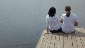 Man en vrouwenzitting op de raadslijst die het meer bekijken stock videobeelden
