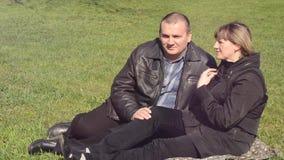 Man en vrouwenzitting op het groene gazon stock videobeelden
