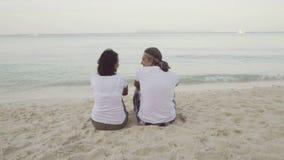 Man en vrouwenzitting op het zand stock footage