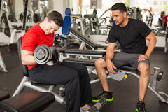 Man encouraging his friend at the gym. Young men spotting and encouraging his male friend while he lifts weights at the gym Royalty Free Stock Photography