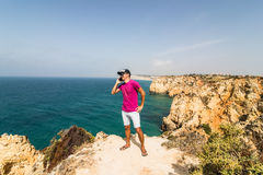 Man in end of the rock near atlantic ocean speak on phone on  summer sunny days Royalty Free Stock Image