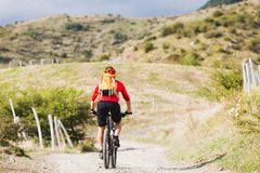 Man enduro mountain biking on country road. Mountain biker riding enduro on bike in summer mountains landscape. Man MTB adventure cycling with backpack on rural stock image