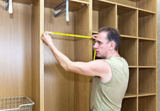 The man is engaged in assemblage of a new wardrobe. Portrait Stock Image