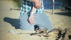 The man is engaged in excavating bones in the sand, Skeleton and archaeological tools. 4k stock footage