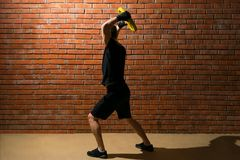Man engaged in fitness, raises a large load over his head against a brick wall background stock images