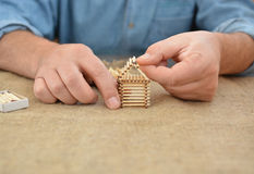 The man is engaged in manual work glue house with matches. Handmade. Blurring background. Free place. Needlework. Hobby. The man is engaged in manual work glue Royalty Free Stock Images