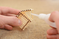 The man is engaged in manual work glue house with matches. Handmade. Blurring background. Free place. Needlework. Hobby. The man is engaged in manual work glue Royalty Free Stock Image
